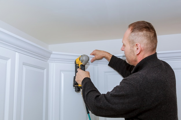 Construction worker using brad nail air gun to crown moulding