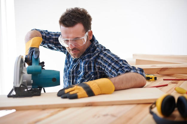 전기 톱을 사용하는 건설 노동자