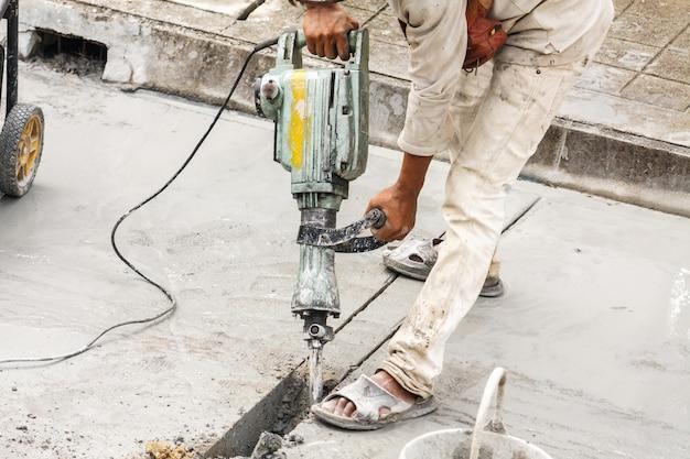 Construction worker using jackhammer drilling concrete surface