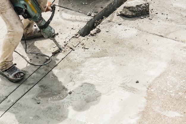 Строитель, используя отбойный молоток, сверля бетонную поверхность