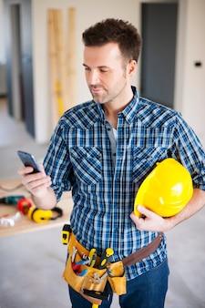 Строитель с помощью мобильного телефона во время работы