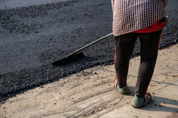 Construction worker using tool spread the hot-mix asphalt road accurately level covering on damaged highway