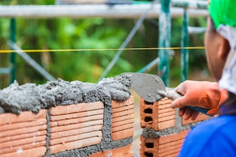 Construction worker using trowel to add cement mortar on top of the bricks wall