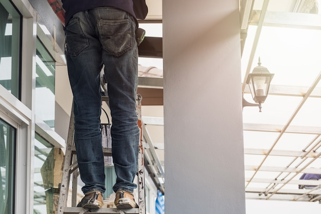 Construction worker wear jean pant standing on aluminium stairs