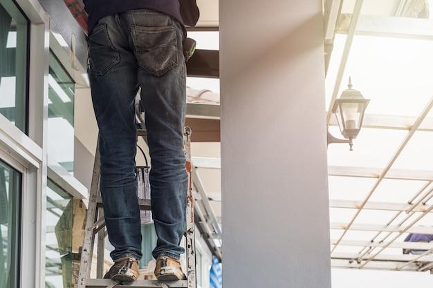 建設作業員はアルミ階段に立っているジーンズパンツを着用
