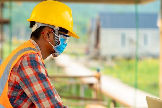 Рабочий-строитель нося защитную маску для того чтобы защитить против covid-19 в строительной площадке, контроль безопасности от эпидемий в концепции строительной площадки.