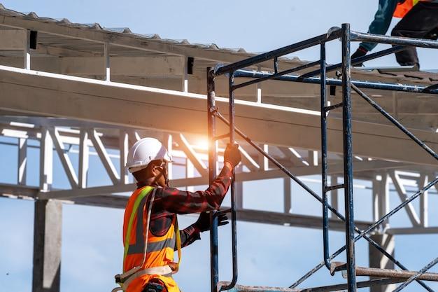 안전 장치와 도구가 있는 안전 라인을 착용한 건설 노동자가 높은 곳에서 작업하는 비계를 오르고 있습니다. 프리미엄 사진
