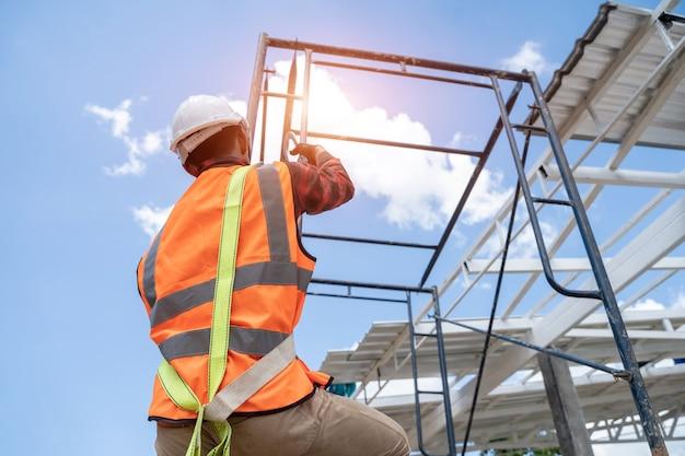 Строительный рабочий в ремнях безопасности и страховочной веревке с инструментами поднимается на строительные леса, работая на высоте.