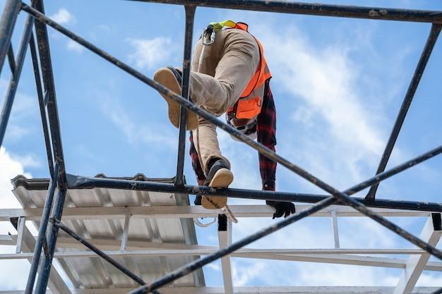 안전 장치와 도구가 있는 안전 라인을 착용한 건설 노동자가 높은 곳에서 작업하는 비계를 오르고 있습니다.