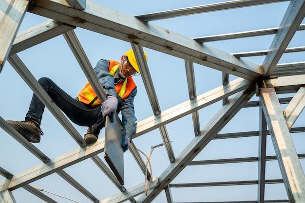 안전 하네스 및 높은 장소에서 일하는 안전 라인을 입고 건설 노동자는 새로운 지붕, 지붕 타일 지붕 공사를 설치합니다.