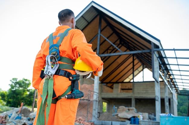 Строительный рабочий в ремнях безопасности и страховочной веревке, работающий на высоком месте, работает на строительной площадке