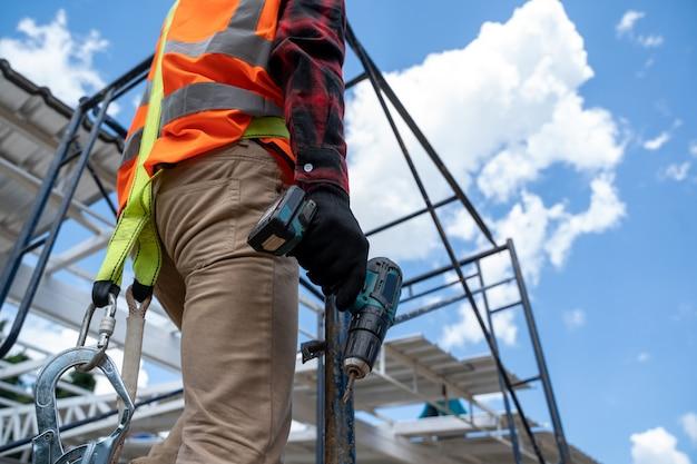 건설 현장에서 비계 작업을 하는 안전 장치와 안전 라인을 착용한 건설 노동자, 비계에 있는 건설 노동자.