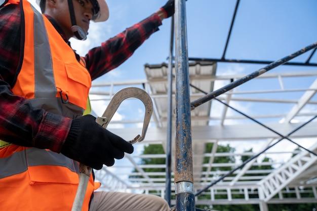 건설 현장에서 비계 작업을 하는 안전 장치와 안전 라인을 착용한 건설 노동자, 높은 곳에서 일합니다.