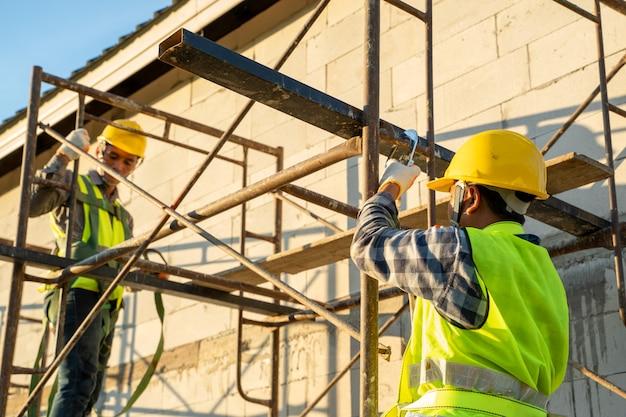 高い場所での作業中に安全ハーネスベルトを身に着けている建設労働者、建設中の住宅の概念。