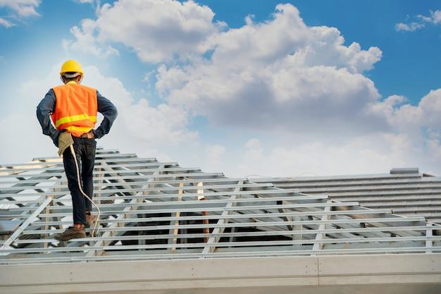 新しい屋根の上にコンクリート屋根瓦を取り付ける作業中に安全ハーネスベルトを身に着けている建設労働者。