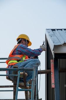 건설중인 집에서 발판에 작업하는 동안 안전 하네스 벨트를 착용하는 건설 노동자.
