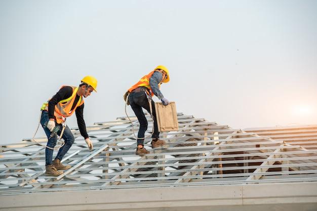 建設現場の建物の屋根構造で作業中に安全ハーネスベルトを身に着けている建設労働者。