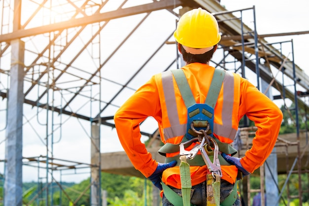 Construction worker wearing safety harness and excavator wearing orange reflective vest standing in front at construction site.