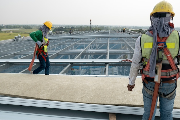 Construction worker wearing safety harness and safety line working on a metal industry roo