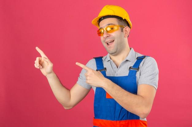 制服の安全ヘルメットとメガネを着て笑顔とピンクに分離された側に2本の手と指で指している建設労働者