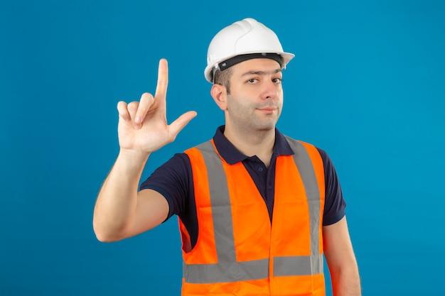 손가락을 가리키는 조끼와 안전 헬멧을 착용하는 건설 노동자와 파란색에 고립 된 화가 식
