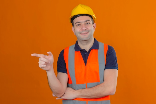 오렌지에 고립 된 얼굴에 미소로 옆으로 그의 검지 손가락을 가리키는 조끼와 노란색 안전 헬멧을 착용하는 건설 노동자