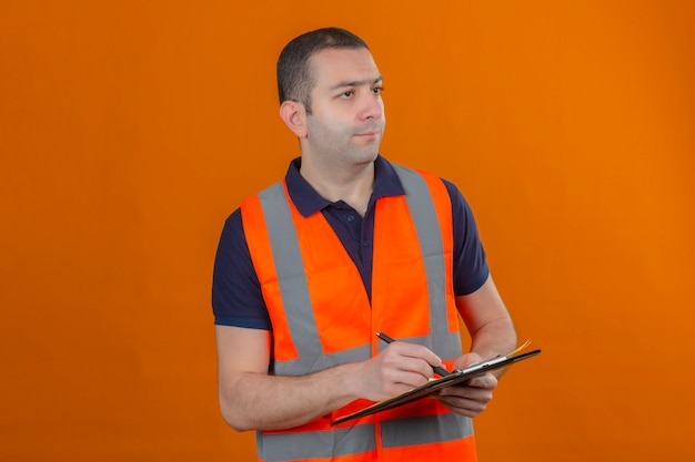 Construction worker wearing vest with a serious face looking away to side holding clipboard with pen in hands isolated on orange