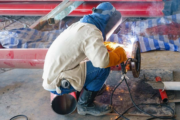 Construction worker welding red steel pipe for fire alarm system in new construction