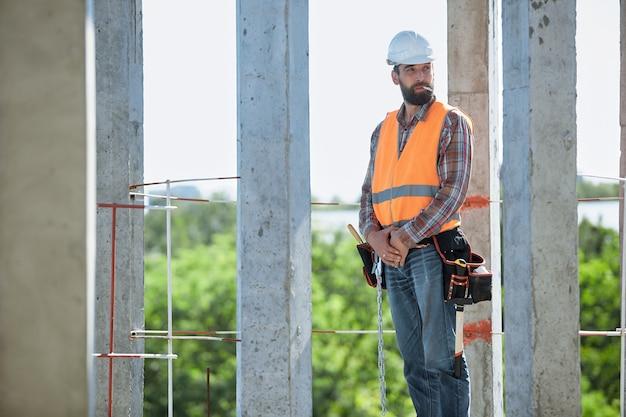 직장에서 담배를 피우는 하드 모자와 보호 조끼를 입고 수염을 가진 건설 노동자