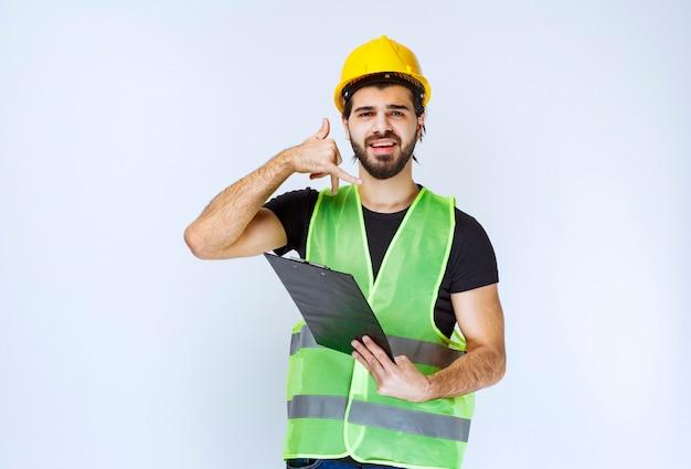 電話を求めるフォルダを持つ建設作業員。