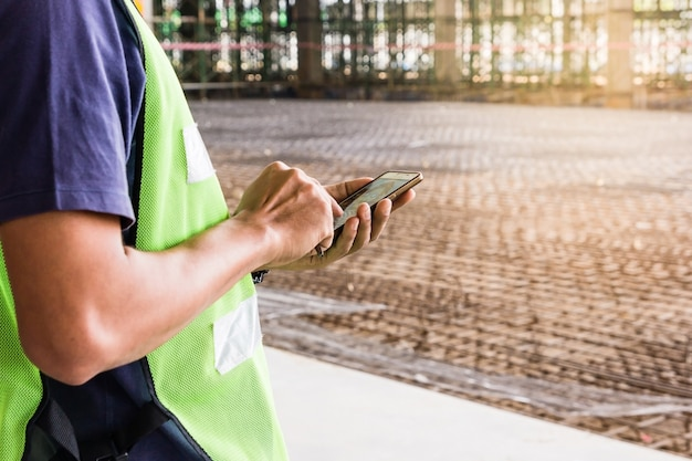 Construction worker with green helmet working on construction site using smartphone