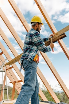 Construction worker with hard hat building the roof of the house Free Photo
