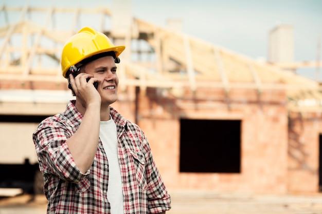 携帯電話を持つ建設労働者