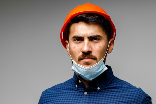 Construction worker with protective mask portrait on grey close up