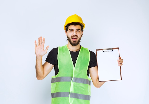Construction worker with a yellow helmet holding a project report.