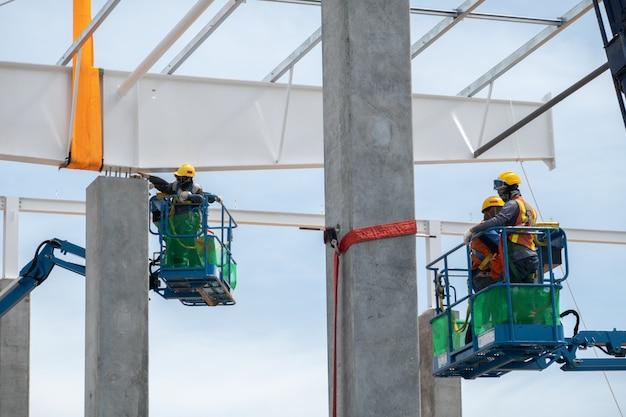 Строительный рабочий, работающий на подъемнике установки стальной балки крыши