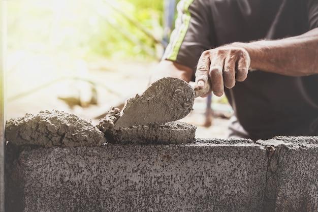 건설 노동자들이 벽돌 블록으로 시멘트 벽을 만들고 있습니다.