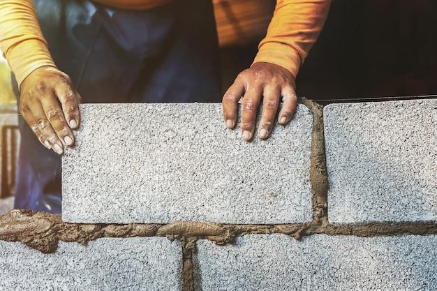 建設作業員はレンガのブロックでセメントの壁を作っています。