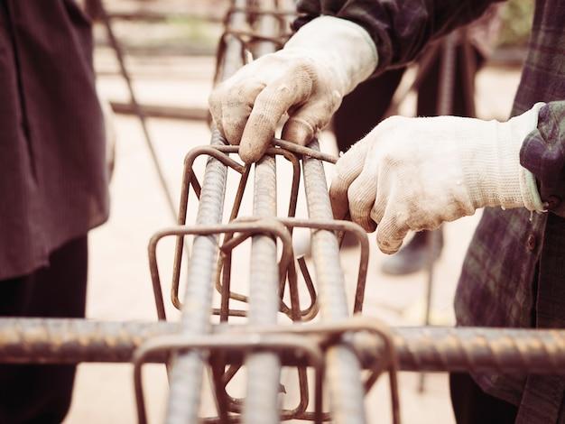 Строители устанавливают стальные стержни в железобетонной колонне