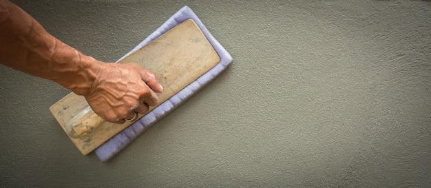 건설 노동자들은 벽을 매끄럽게하기 위해 스폰지와 회 반죽 흙손을 사용하고 있습니다.