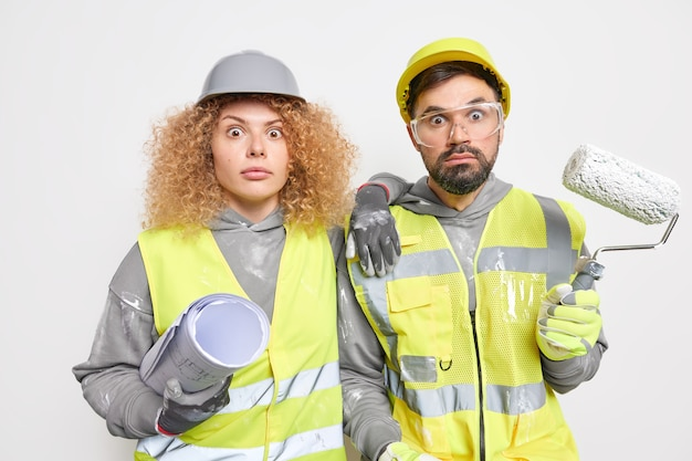 Construction workers decorate apartment hold painting roller and paper blueprint wear uniform