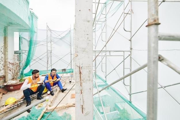 昼食を食べている建設労働者