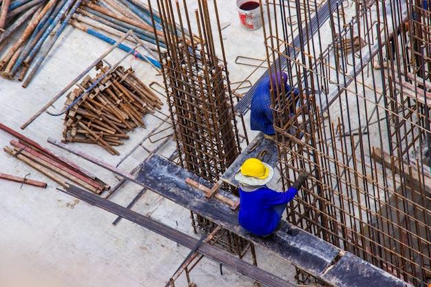 건설 지역 건축 현장에서 큰 강철 막대 보강 바를 조작하는 건설 노동자.