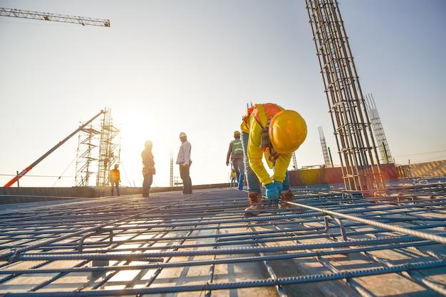 Строители, производящие стальной арматурный стержень на строительной площадке