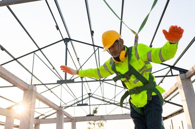 Строители падают с высоты, но им на помощь приходит безопасность. концепция предотвращения опасности с высоты с помощью безопасности на строительной площадке.