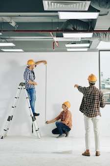Construction workers measuring length
