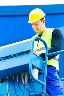 Строители или машинист крана на строительной площадке управляют гидравлической подъемной рампой с пультом управления Premium Фотографии