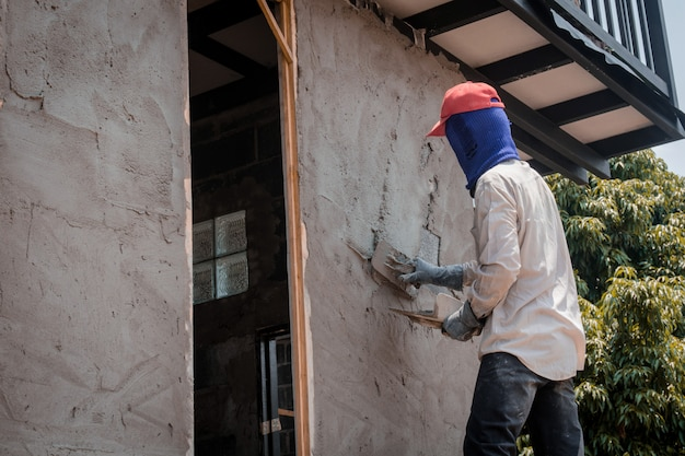 Строители оштукатуривают стены здания цементной штукатуркой