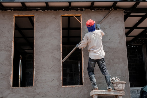 Construction workers plastering building wall using cement plaster