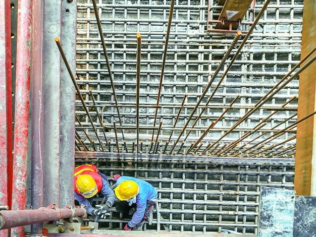 Строители сидят на стали с бетонным фундаментом и проверяют круглый бар